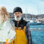 Portrait of senior fisherman with plastic bottles in fishing net. Environmental pollution concept.