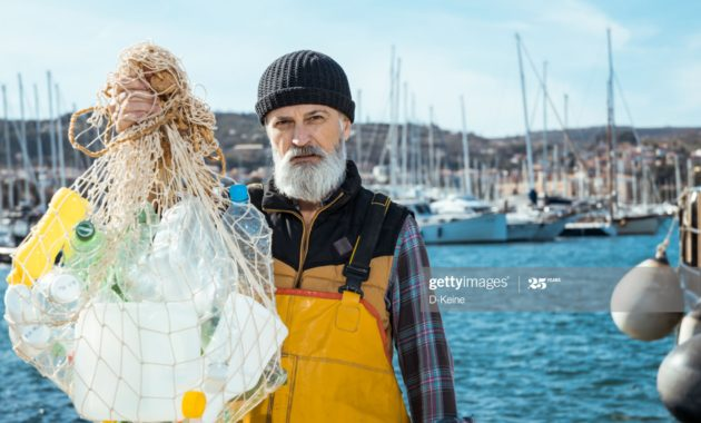 Portrait of senior fisherman with plastic bottles in fishing net. Environmental pollution concept.